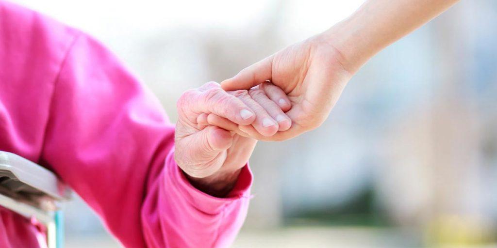 Main aidant une personne âgée